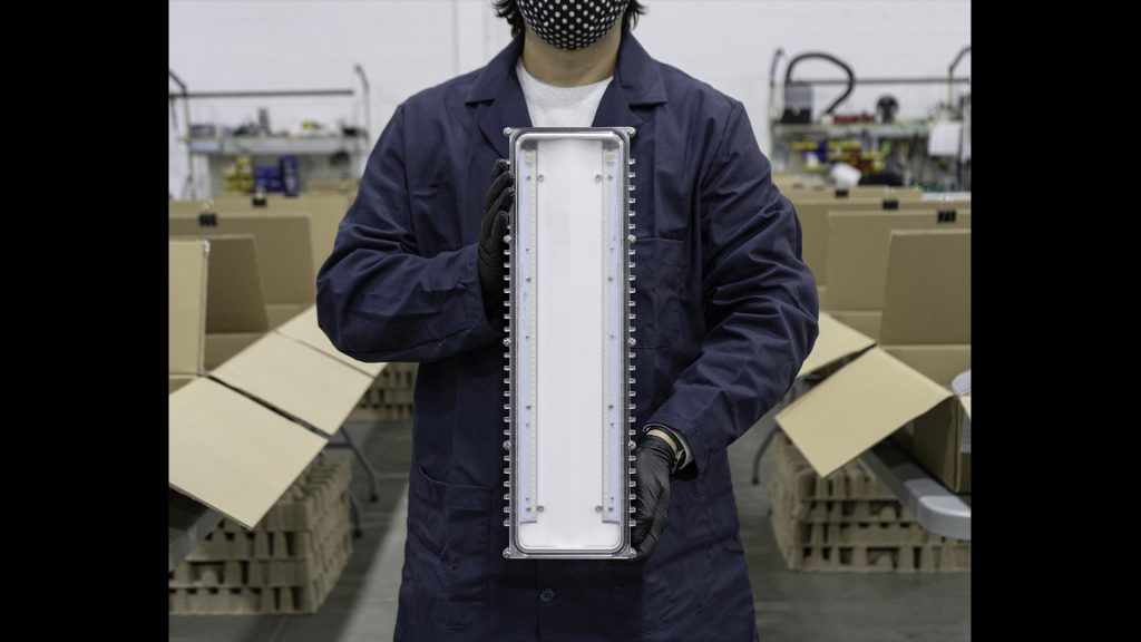 Nemalux employee holding a BL Series industrial LED Luminaire, marine and hazardous location class I div 2 (c1d2) approved, vapour tight fluorescent light replacement